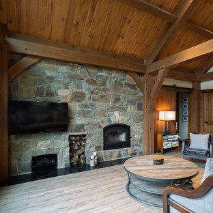 Großes, Offenes Uriges Wohnzimmer mit beiger Wandfarbe, Linoleum, Kaminofen, Kaminumrandung aus Stein, Wand-TV und braunem Boden in Sonstige