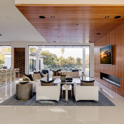 Inspiration for a huge contemporary open concept porcelain tile and white floor family room remodel in Los Angeles with brown walls, a standard fireplace, a wood fireplace surround and a wall-mounted tv
