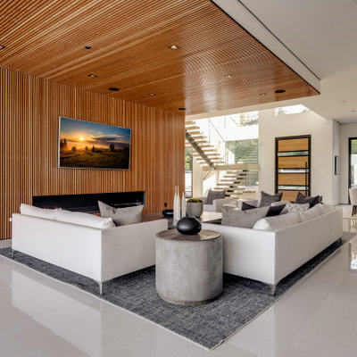 Huge trendy open concept porcelain tile and white floor family room photo in Los Angeles with a wood fireplace surround, a wall-mounted tv, brown walls and a standard fireplace