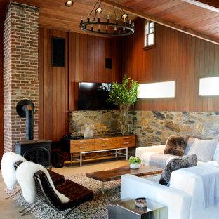 ニューヨークのコンテンポラリースタイルのおしゃれなファミリールーム (茶色い壁、コンクリートの床、薪ストーブ、レンガの暖炉まわり、壁掛け型テレビ) の写真
