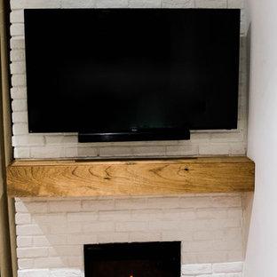 Immagine di un soggiorno stile rurale di medie dimensioni e stile loft con libreria, pareti bianche, parquet scuro, camino sospeso, cornice del camino in mattoni, TV nascosta e pavimento marrone