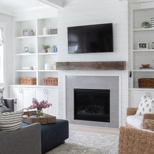Idées déco pour une grand salle de séjour campagne fermée avec un mur blanc, un sol en bois clair, une cheminée standard, un manteau de cheminée en carrelage, un téléviseur fixé au mur et un sol beige.
