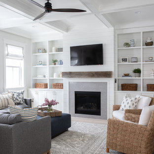 Design ideas for a large country enclosed family room in Chicago with white walls, light hardwood floors, a standard fireplace, a tile fireplace surround, a wall-mounted tv and beige floor.