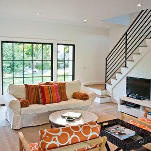 Imagen de sala de estar campestre con paredes blancas, suelo de madera en tonos medios y televisor independiente
