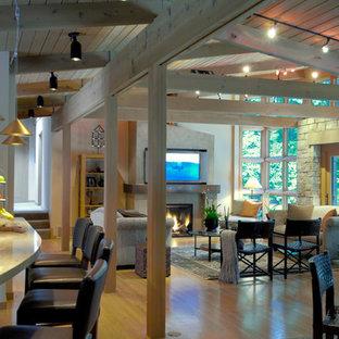 Immagine di un soggiorno stile americano aperto e di medie dimensioni con parquet chiaro, pareti bianche, camino classico, cornice del camino in cemento, TV nascosta e pavimento marrone