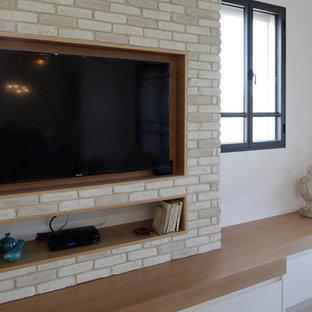 他の地域の大きいコンテンポラリースタイルのおしゃれなファミリールーム (ベージュの壁、セラミックタイルの床、コーナー設置型暖炉、レンガの暖炉まわり、埋込式メディアウォール) の写真