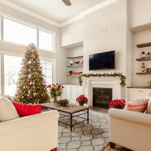 Ispirazione per un grande soggiorno classico aperto con pareti beige, pavimento in laminato, camino classico, cornice del camino piastrellata e TV a parete