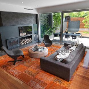 Cette photo montre une grande salle de séjour tendance ouverte avec un mur noir, un sol en bois brun, un téléviseur fixé au mur, un poêle à bois, un manteau de cheminée en métal et un sol orange.