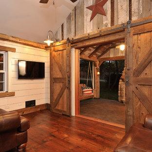 Esempio di un soggiorno rustico chiuso e di medie dimensioni con pareti beige, parquet scuro e TV a parete