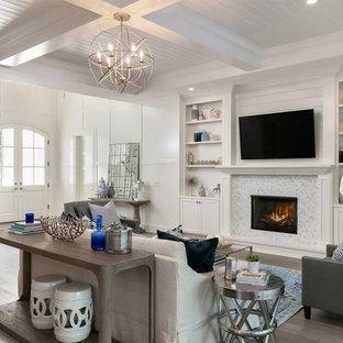 Idée de décoration pour une salle de séjour marine de taille moyenne et ouverte avec un mur blanc, un manteau de cheminée en carrelage, un téléviseur fixé au mur, un sol en bois clair, une cheminée standard et un sol marron.