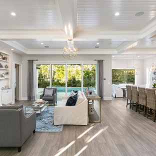 Ispirazione per un soggiorno stile marino di medie dimensioni e aperto con pareti bianche, camino classico, TV a parete, cornice del camino piastrellata, pavimento marrone e parquet scuro