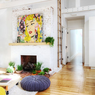 Inspiration for a mid-sized eclectic light wood floor family room remodel in Indianapolis with white walls, a standard fireplace and a brick fireplace