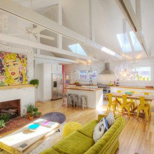 Imagen de sala de estar abierta, bohemia, de tamaño medio, con paredes blancas, suelo de madera clara, chimenea tradicional, marco de chimenea de ladrillo y televisor colgado en la pared