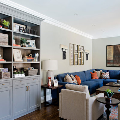 Family room - mid-sized transitional medium tone wood floor and brown floor family room idea in Toronto with gray walls, a standard fireplace, a wood fireplace surround and a wall-mounted tv