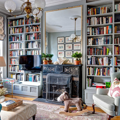 Mid-sized ornate medium tone wood floor family room library photo in New York with green walls and a stone fireplace