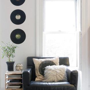 ニューヨークの中サイズのコンテンポラリースタイルのおしゃれなファミリールーム (ライブラリー、白い壁、淡色無垢フローリング、標準型暖炉、レンガの暖炉まわり、据え置き型テレビ、白い床) の写真