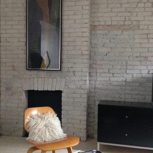 ニューヨークの中くらいのコンテンポラリースタイルのおしゃれなロフトリビング (ライブラリー、白い壁、淡色無垢フローリング、標準型暖炉、レンガの暖炉まわり、据え置き型テレビ) の写真