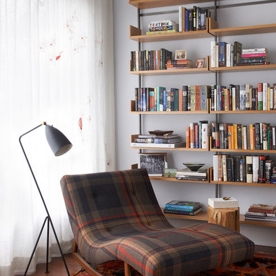 Trendy medium tone wood floor and brown floor family room library photo in New York with white walls