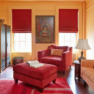 Cette photo montre une salle de séjour chic fermée avec un mur orange, un sol en bois peint, une cheminée standard, un manteau de cheminée en pierre et un téléviseur fixé au mur.