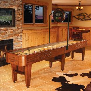 Diseño de sala de juegos en casa abierta, rural, grande, con paredes multicolor, suelo de travertino, chimenea tradicional, marco de chimenea de ladrillo y televisor colgado en la pared