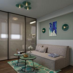 Imagen de sala de estar con rincón musical cerrada, actual, pequeña, con paredes verdes, suelo de bambú, televisor colgado en la pared y suelo marrón
