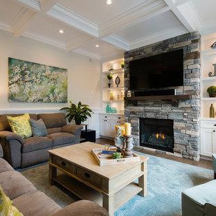 Imagen de sala de estar abierta, clásica, grande, con paredes grises, suelo de madera en tonos medios, chimenea tradicional, marco de chimenea de piedra y pared multimedia