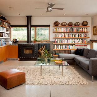Modelo de sala de estar abierta, contemporánea, pequeña, con suelo de cemento, pared multimedia, paredes blancas y chimenea tradicional