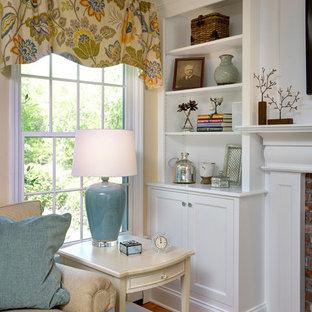 Inspiration pour une salle de séjour avec une bibliothèque ou un coin lecture méditerranéenne de taille moyenne et ouverte avec un mur beige, un sol en bois clair, un manteau de cheminée en brique et un téléviseur fixé au mur.