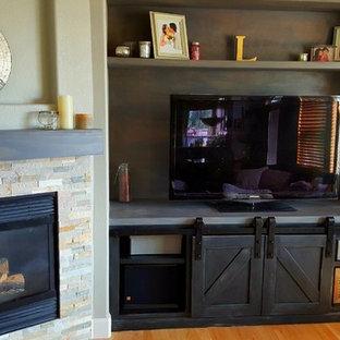 Imagen de sala de estar abierta, tradicional renovada, pequeña, con paredes grises, suelo de madera clara, chimenea de esquina, marco de chimenea de piedra y televisor independiente