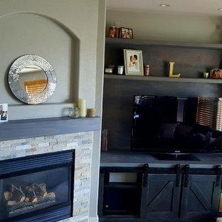 Diseño de sala de estar abierta, clásica renovada, pequeña, con paredes grises, suelo de madera clara, chimenea de esquina, marco de chimenea de piedra y televisor independiente