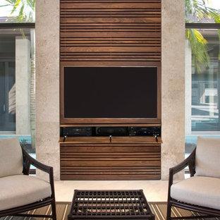 マイアミの中サイズのトロピカルスタイルのおしゃれなファミリールーム (ベージュの壁、磁器タイルの床、暖炉なし、埋込式メディアウォール、ベージュの床) の写真