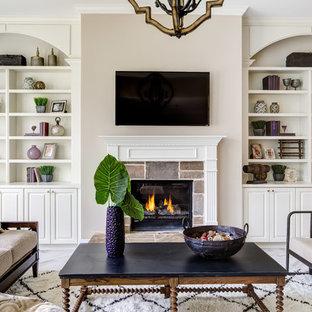 アトランタのトラディショナルスタイルのおしゃれなファミリールーム (ベージュの壁、標準型暖炉、石材の暖炉まわり、壁掛け型テレビ) の写真