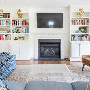 Стильный дизайн: гостиная комната в классическом стиле с белыми стенами, паркетным полом среднего тона, телевизором на стене, стандартным камином и коричневым полом - последний тренд