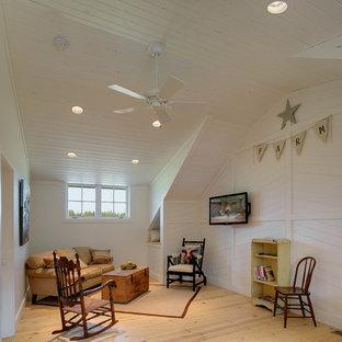 Foto de sala de estar cerrada, campestre, con paredes blancas, suelo de madera clara y televisor colgado en la pared