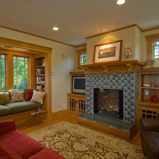 Modelo de sala de estar de estilo americano, de tamaño medio, con marco de chimenea de baldosas y/o azulejos, paredes beige, suelo de madera en tonos medios y chimenea tradicional