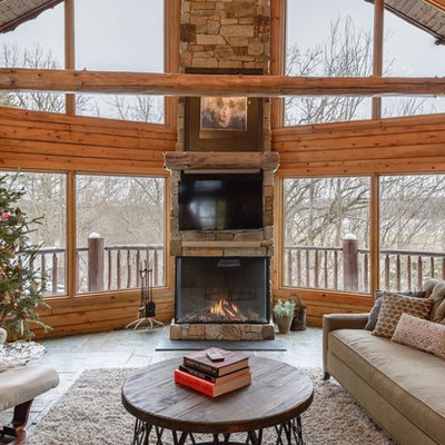 Inspiration for a rustic family room remodel in Minneapolis with a standard fireplace, a stone fireplace and a wall-mounted tv