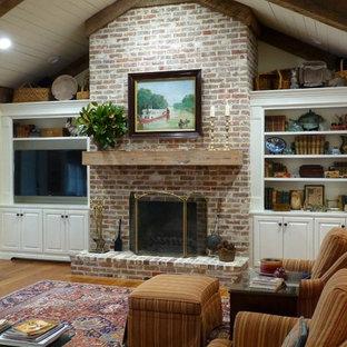 Réalisation d'une grande salle de séjour tradition ouverte avec un téléviseur encastré, un mur jaune, un sol en bois foncé, une cheminée standard, un manteau de cheminée en brique et un sol marron.