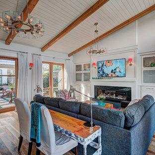 Modelo de sala de estar abierta, campestre, de tamaño medio, con paredes blancas, suelo de madera en tonos medios, televisor colgado en la pared, suelo multicolor y chimenea lineal