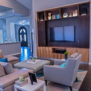 Esempio di un grande soggiorno minimalista aperto con pareti grigie, parquet scuro, nessun camino e parete attrezzata
