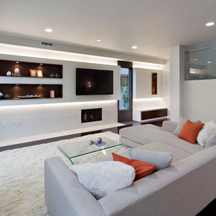Family room - large contemporary open concept dark wood floor family room idea in Los Angeles with white walls, a standard fireplace, a tile fireplace and a wall-mounted tv