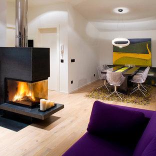 バルセロナの大きいコンテンポラリースタイルのおしゃれなファミリールーム (白い壁、淡色無垢フローリング、両方向型暖炉、金属の暖炉まわり、テレビなし) の写真