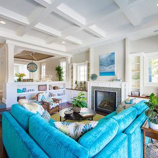 ロサンゼルスの大きいビーチスタイルのおしゃれなファミリールーム (標準型暖炉、タイルの暖炉まわり、テレビなし、グレーの壁、濃色無垢フローリング、茶色い床) の写真