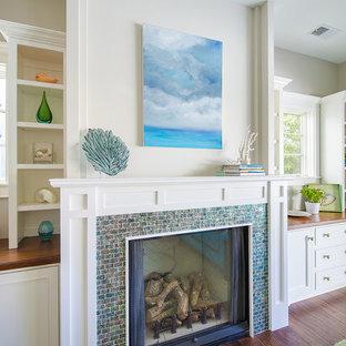 ロサンゼルスのビーチスタイルのおしゃれなファミリールーム (白い壁、無垢フローリング、標準型暖炉、タイルの暖炉まわり、テレビなし) の写真