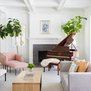 Idées déco pour une grande salle de séjour bord de mer ouverte avec un mur blanc, un sol en bois clair, une cheminée standard, un manteau de cheminée en pierre et une salle de musique.