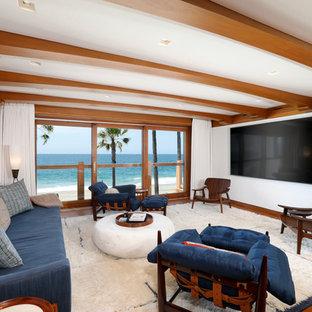 Aménagement d'une salle de séjour bord de mer de taille moyenne et fermée avec un mur blanc, un sol en bois brun, un téléviseur fixé au mur, un sol marron et aucune cheminée.