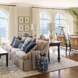 Foto di un soggiorno stile marinaro di medie dimensioni e aperto con pareti beige, parquet scuro, camino classico, cornice del camino in intonaco e TV a parete