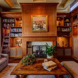 Imagen de sala de estar con biblioteca de estilo americano con suelo de madera oscura y chimenea tradicional