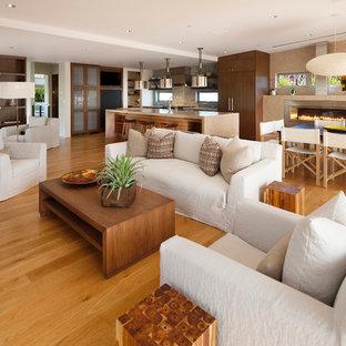 サンタバーバラの広いコンテンポラリースタイルのおしゃれなオープンリビング (淡色無垢フローリング、白い壁、オレンジの床) の写真