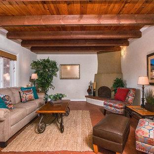 アルバカーキの中サイズのサンタフェスタイルのおしゃれな独立型ファミリールーム (ベージュの壁、レンガの床、コーナー設置型暖炉、レンガの暖炉まわり) の写真