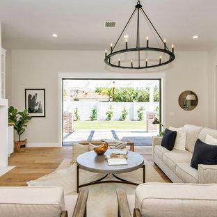 Idée de décoration pour une grande salle de séjour craftsman ouverte avec un mur gris, un sol en bois clair, une cheminée standard, un manteau de cheminée en pierre, un téléviseur fixé au mur et un sol marron.